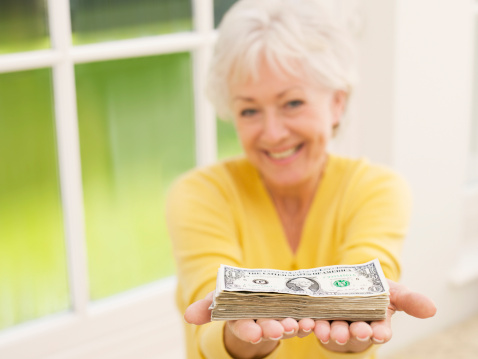 Woman holding out stack of one dollar bills