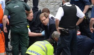 Conservative MP Tobias Ellwood (centre) helps emergency services attend to a police officer outside the Palace of Westminster, London, after a policeman was stabbed and his apparent attacker shot by officers in a major security incident at the Houses of Parliament. PRESS ASSOCIATION Photo. Picture date: Wednesday March 22, 2017. See PA story POLICE Westminster. Photo credit should read: Stefan Rousseau/PA Wire